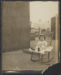 Unidentified baby on a rocking chair on a rooftop, undated : photograph