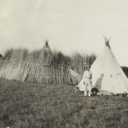 Man in a Yard with Two Tipi...