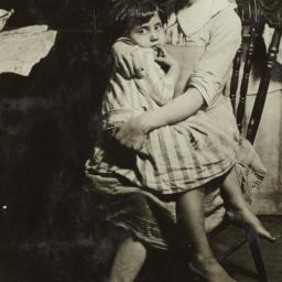 Girl holding Child on Chair