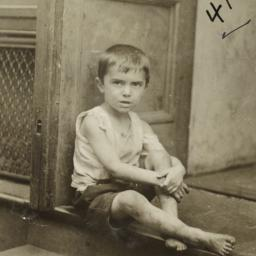 Boy Sitting at Entrance to ...