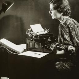 Woman Writing on Typewriter